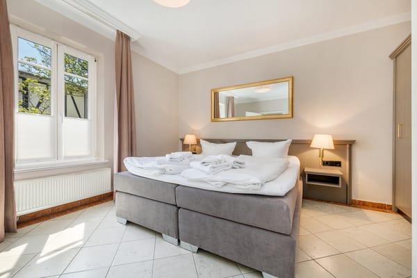 Das Schlafzimmer mit Doppelbett, Verdunkelungsgardinen und großem Kleiderschrank.