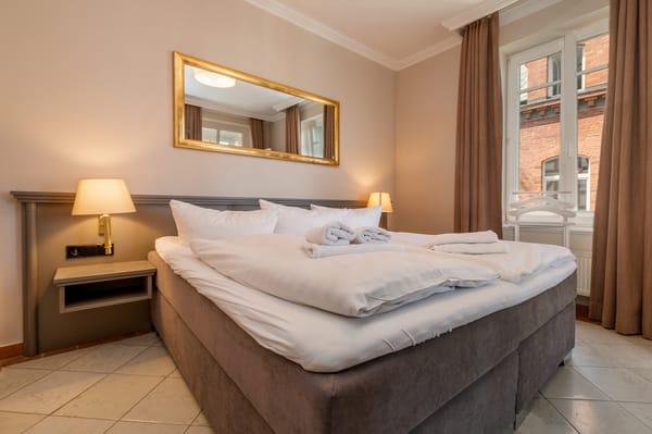 Das Schlafzimmer mit Doppelbett, Kleiderschrank und Verdunkelungsgardinen am Fenster.