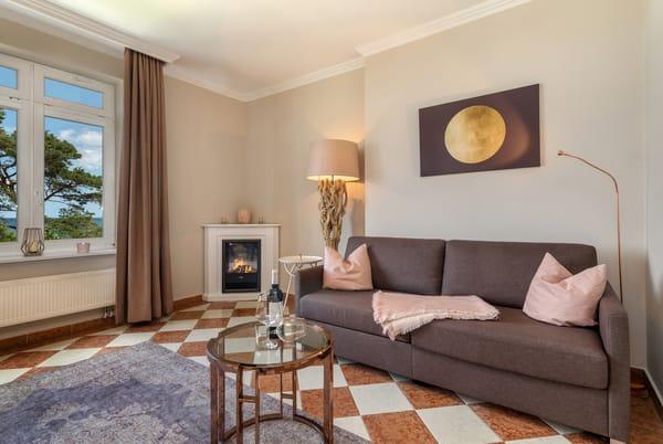 Der elektrische Kamin bereitet Urlaubsstimmung. Auf der Couch kann aufgebettet werden.