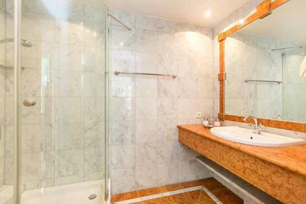 Das schöne marmorgeflieste Bad mit Echtglasdusche, Fön und WC.