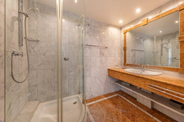 Das schöne marmorgeflieste Bad mit Dusche, WC und Fön.