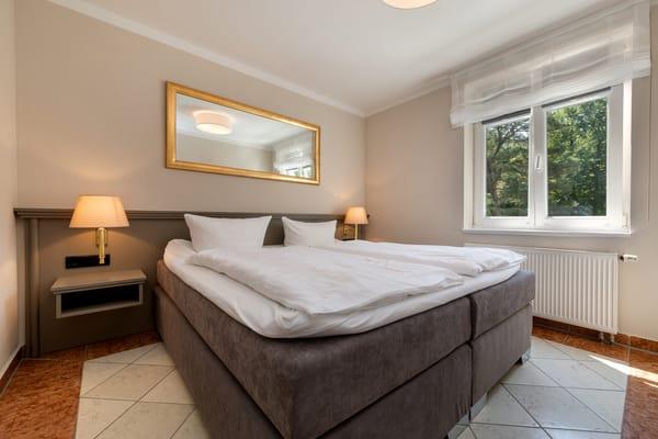 Das Schlafzimmer hat Doppelbett und Verdunkelungsplissees an den Fenstern.