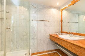 Hier der Blick in das marmorgeflieste Bad mit Echtglasdusche und WC.