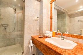 Das schicke Duschbad ist mit Marmor gefliest.