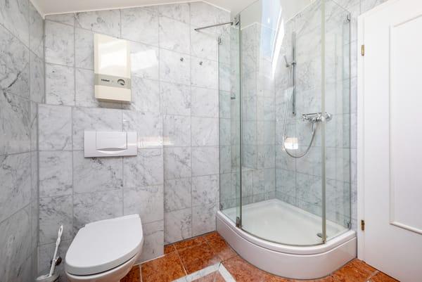 Das marmorgeflieste Bad mit Dusche, WC und Fön.