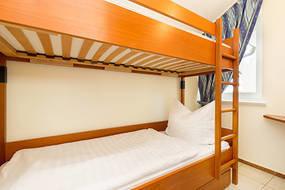 Das Foto zeigt das kleine Kinderzimmer mit Etagenbett. Die Matratzen im Etagenbett haben die Maße 0,70 x 1,80m.