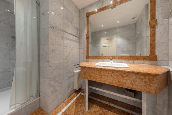 Das marmorgeflieste Bad mit Dusche ...