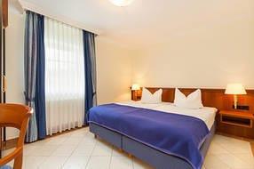 Das große Schlafzimmer mit Doppelbett und Kleiderschrank.