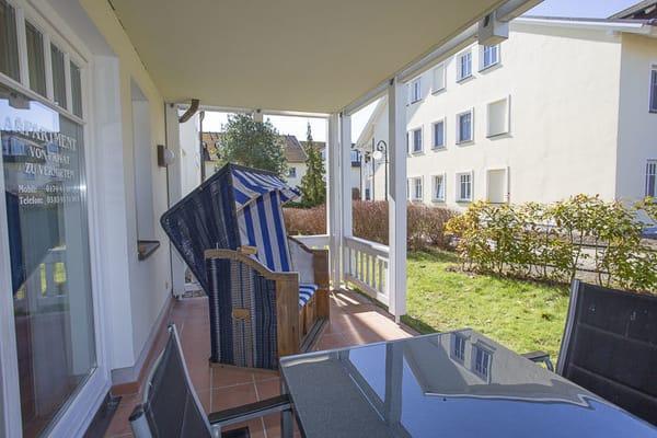 Geräumige Terrasse mit Süd-Westlage, großem Tisch, fünf Stühle und einem Strandkorb.
