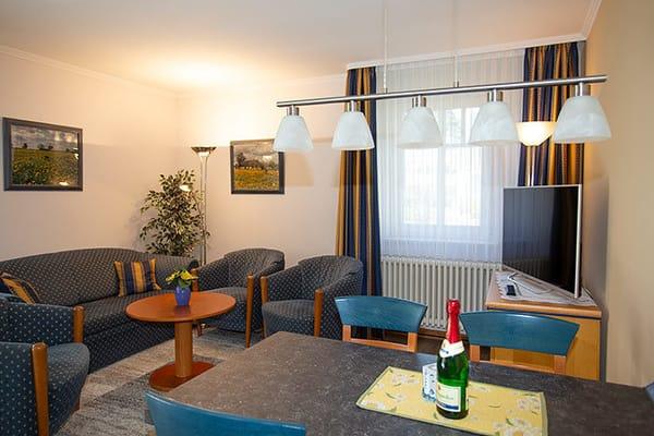 Großer Wohnbereich mit Esstisch und Flachbildfernseher