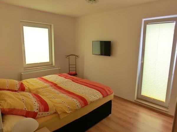 Schlafzimmer mit Doppelbett und SAT-TV