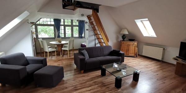 Blick zur Veranda mit Essecke und Schlafbereich, die Treppe führt zum Spitzboden mit zwei Schlafplätzen