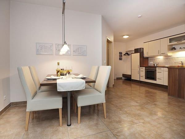 Der Wohnbereich wird mit einem Essplatz und einer offenen Küchenzeile - die keine Wünsche offen lässt -  optimal ergänzt.