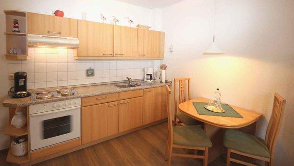 Die Küchenzeile ist mit einem Backofen, Kühlschrank, Kochfeld, Mikrowelle, Kaffeemaschine, Wasserkocher, Toaster und diversen Kleingeräten ausgestattet.
