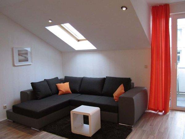 Im Wohnraum gibt es eine gemütliche Eck-Couch mit Schlaffunktion für die 3. und 4. Person sowie ein Flachbildfernseher und DVD-Player. Ein geschützter in Richtung Süden liegender Balkon schließt sich