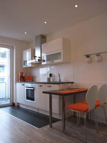 Die Küchenzeile ist mit einem Backofen, Kühlschrank, Cerankochfeld, Geschirrspüler, Kaffeemaschine, Toaster und Wasserkocher ausgestattet.