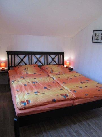 Das Schlafzimmer verfügt über ein Doppelbett, einen 3-türigen Kleiderschrank mit Spiegel sowie ein TV-Gerät.
