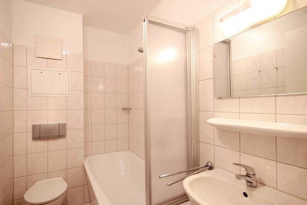Badezimmer mit Waschtisch, Badewanne mit Duschabtrennung und WC