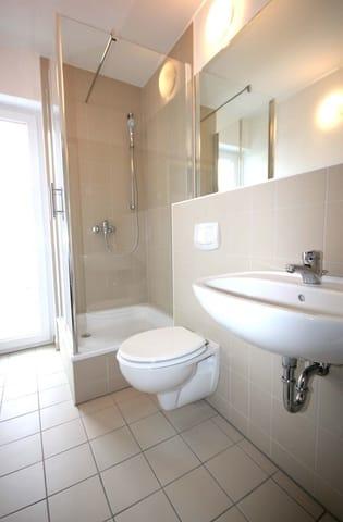 Das Tageslichtbad ist ausgestattet mit Waschtisch, Glasdusche und WC.