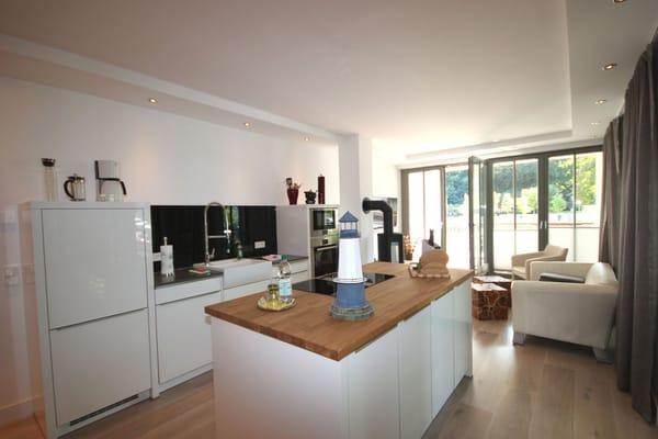 Die hochwertige Inselküche ist komplett mit Geschirrspülmaschine, Ceranfeld, Backofen, Mikrowelle, Kühlschrank mit Gefrierfach und weiteren Küchenhelfern ausgestattet.