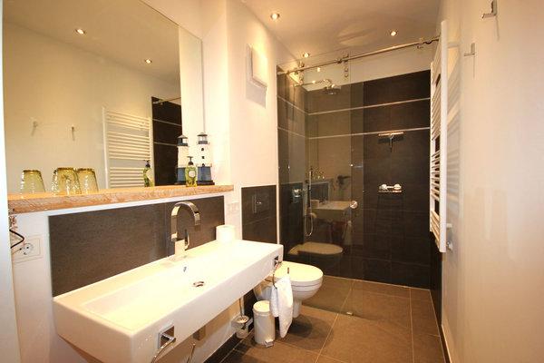 Es gibt zwei Badezimmer mit Regendusche, Waschtisch und WC.