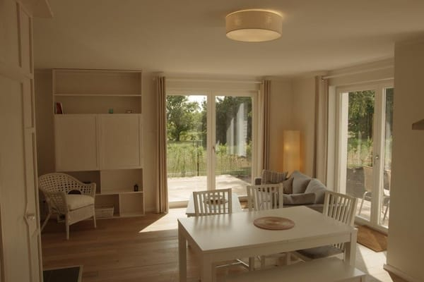 heller Wohnraum mit Küche, Kamin und Eichenparkett