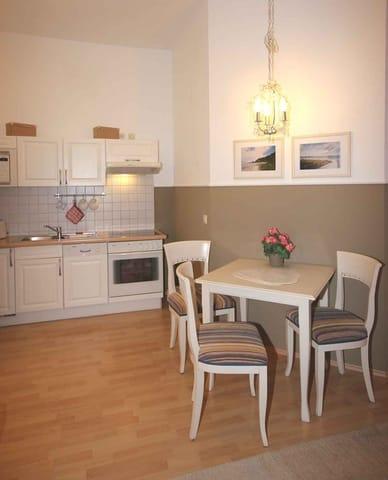 Im Wohnraum befindet sich eine komplett ausgestattete Küchenzeile mit Geschirrspüler, Backofen, Ceranfeld, Kühlschrank, Mikrowelle, Kaffeemaschine, Wasserkocher und Toaster.
