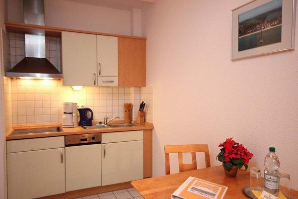 Küchenzeile ist mit Kühlschrank, Cerankochfeld, Geschirrspüler und diversen Kleingeräten