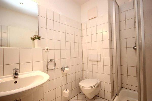 das Badezimmer mit Waschtisch, Dusche und WC