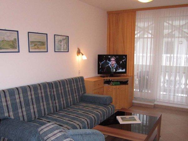 Neben dem gemütlichen Sofa finden Sie im Wohnraum einen separaten Eßplatz. Zur technischen Ausstattung gehören TV und Radio.