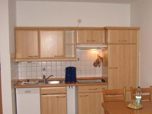 Die im Wohnraum integrierte Kochecke ist mit Kühlschrank, Geschirrspüler und weiteren Elektrogeräten ausgestattet.