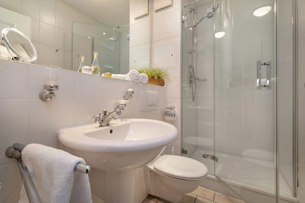 Hier der Blick in das Bad mit Echtglasdusche, Fön, Handtuchtrockner und WC.
