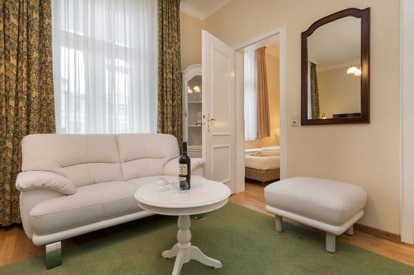 Eine bequeme Couch mit Fußhocker lädt zum Entspannen ein.