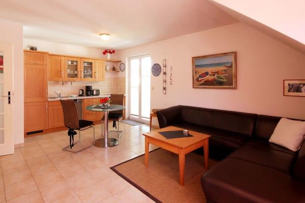 Im Wohnzimmer ist die komplett eingerichtete Küche mit Essplatz integriert.