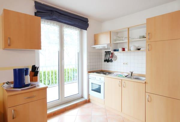 Die Küchenzeile beinhaltet u.a. ein Kochfeld, Backofen, Kühlschrank, Kaffeemaschine und Toaster.