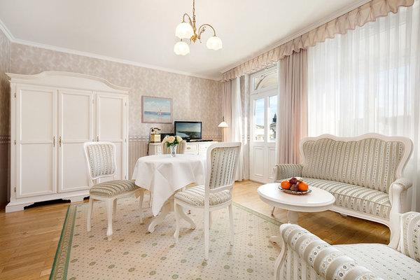 """Herzlich willkommen in der Ferienwohnung """"Sissy""""! Hier das Wohnzimmer mit Austritt zum Balkon."""