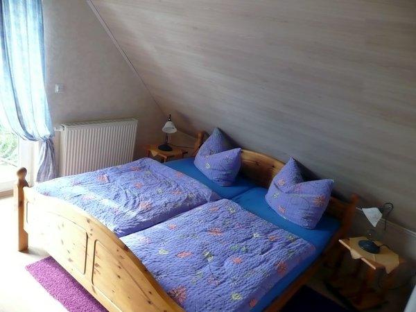 Schlafraum mit Doppelbett und Sicht auf Balkon