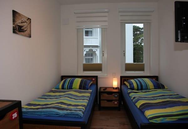 kleines Schlafzimmer Hauptschlafzimmer mit Flachbildfernseher sowie Kleiderschrank und Kommode.