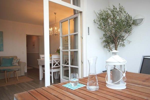 Zugang vom Wohnzimmer zum überdachten Balkon mit dazugehörigen Möbeln