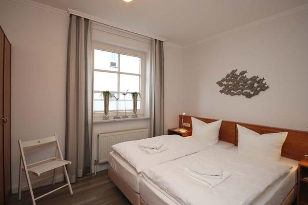 Schlafzimmer mit großzügigem Doppelbett (Gesamtgröße von 1,80 m x 2,00 m) sowie getrennten Matratzen, großem Kleiderschrank, Radiowecker und zusätzlichem Verdunklungsrollo