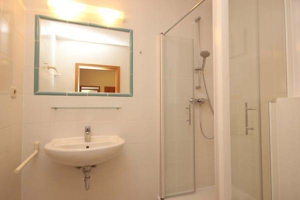Badezimmer finden Sie Waschtisch, Dusche und WC