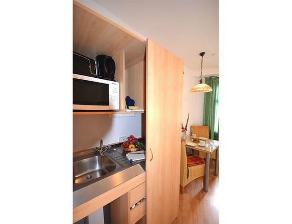 Die exklusive Pantryküche ist mit allem bestückt, was Sie für die Zubereitung Ihrer Lieblingsspeisen benötigen. Neben zwei Kochplatten und einem Kühlschrank findet sich auch eine Mikrowelle.