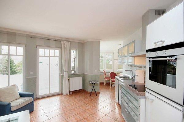Die Küchenzeile beinhaltet u.a. ein Cerankochfeld, Backofen und weitere Elektrogeräte.