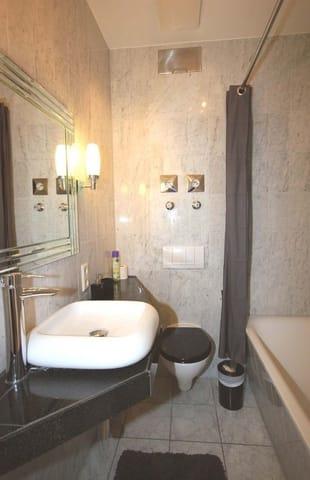 Badezimmer mit Waschtisch, Badewanne, WC und Fön