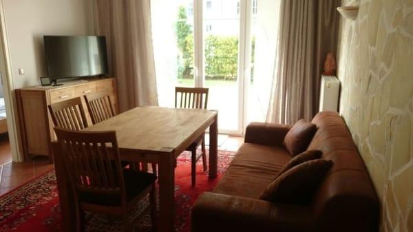 Wohnzimmer mit großem Esstisch und Blick auf Terrasse und Garten, Sofa, Kommode, TV