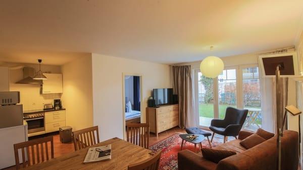 Wohnzimmer mit großem Esstisch, offener Küche und Blick auf Terrasse und Garten, Sofa, Kommode, TV