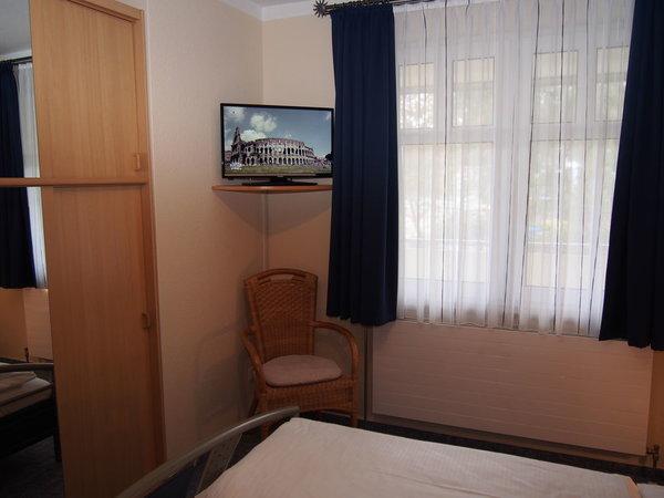 Schlafzimmer mit Spiegelschrank und TV-Gerät