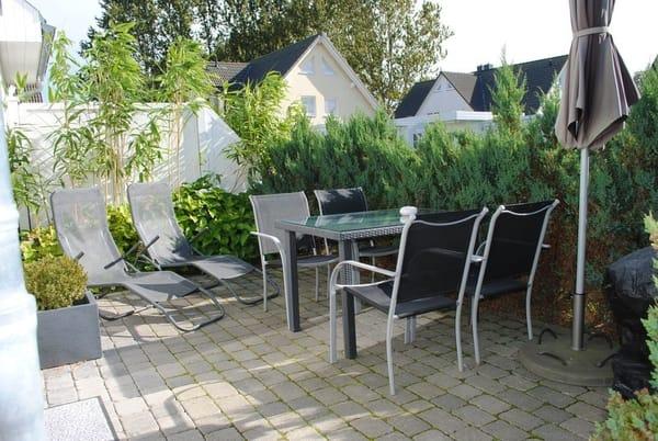 große Sonnen-Terrasse mit Sitzgruppe, Wellnessliegen, Sonnenschirm und Grill