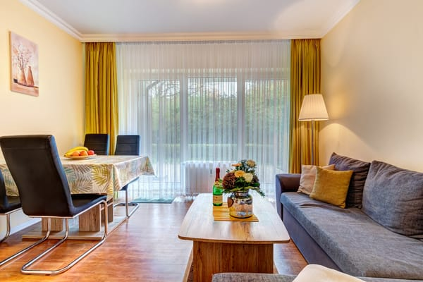 Wohnzimmer mit Schlafcouch, Essplatz, Flat-TV und Zugang auf die Terrasse.