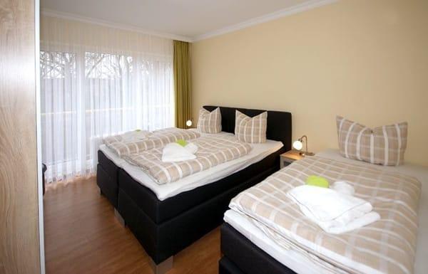 das Schlafzimmer mit Doppel- und Einzelbett und Zugang auf die Terrasse